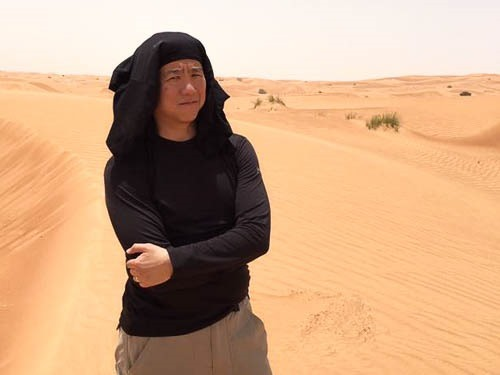 Me standing in the desert with a black shirt on my head