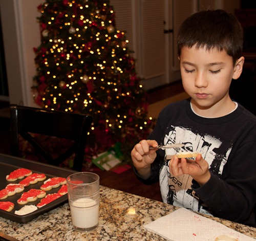 Michael decorating his snowman cookie army.