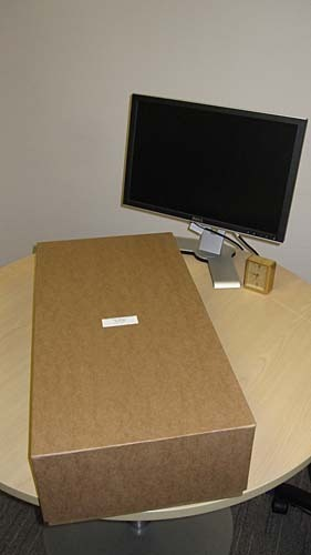 Big brown cardboard box on a round conference table with a flat panel display. The box is almost as long as the diameter of the table.