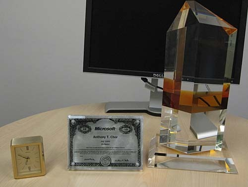 A small gold clock, a silver Microsoft stock certificate, and a tall clear crystal with an orange band across the middle.
