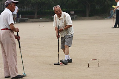 A man ready to hit his ball with a mallet while another watches.