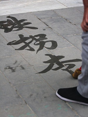 Man practicing Chinese calligraphy on ground.