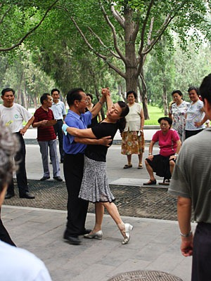 Tango dance instructors surrounded by students.