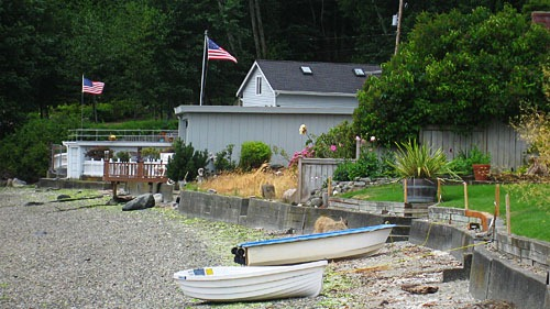 Rowboats on a rocky beach with houses in the background at low tide.