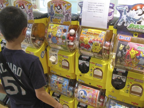 Andrew in front of a row of capsule machines at Pokemon Center Tokyo