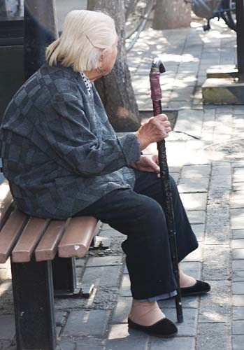Older Chinese woman sitting on a bench. Her feet were bound.