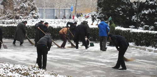 Clearing snow in Beijing with shovels and brooms
