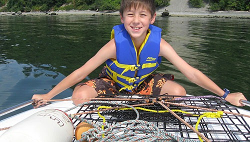 Andrew in a life jacket holding the flattened crab traps down on the foredeck.