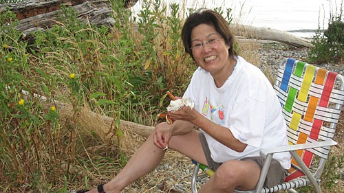 Barbi sitting on a folding chair next to tall grass eating crab with a big smile on her face.