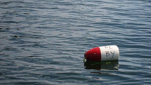 Red and white crab trap buoy with the initials KE and BY.