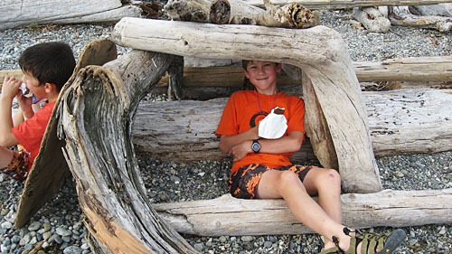 Andrew sitting under a driftwood shelter holding an ice cream bar. Michael is sitting to his right with a bar too.