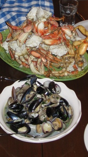 A plate heaped with boiled crab halves and a bowl full of clams and mussels.