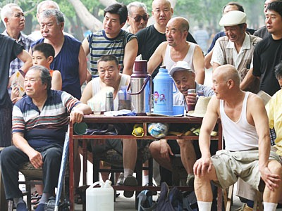 Table with tea thermoses on top, surrounded by older men.