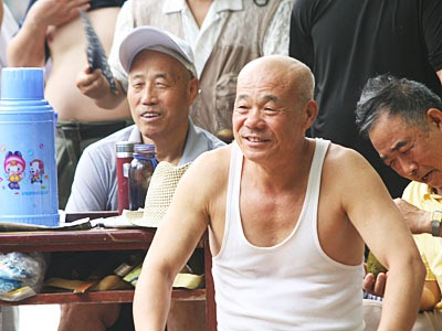 Old, smiling man in a white tank top t-shirt watching the match.