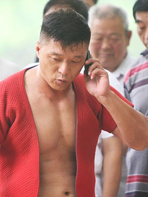 Zoomed in shot of a muscled wrestler in red talking on his cellphone.