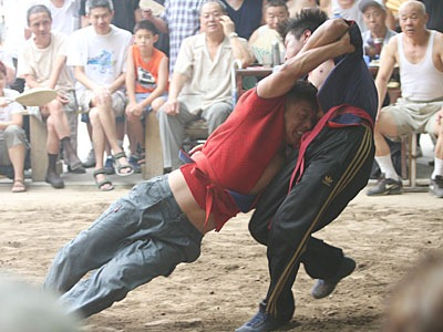 Wrestler in red pulling down a wrestler in blue.