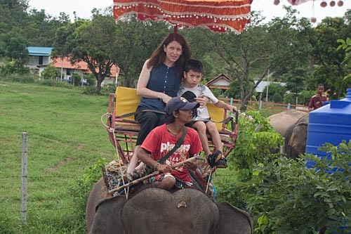 Michelle and and an unhappy Michael riding on an elephant.