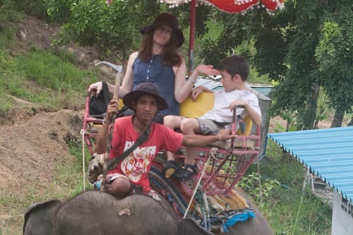 Michael chillaxing on an elephant as Michelle smiles.