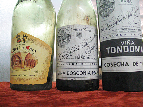 Three old wine bottles: 1947 Bourdy, 1942 Bosconia, and 1942 Tondonia.