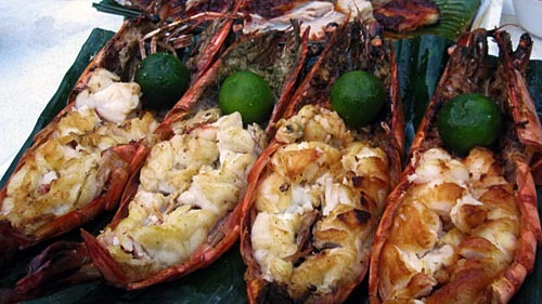 Huge grilled prawns split open, with small whole limes.