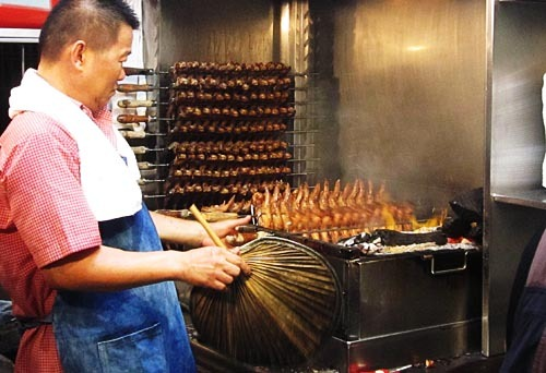 Master grilling chicken wings, holding a fan.