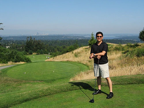 Me standing on the teebox with a panoramic view of Seattle behind me.