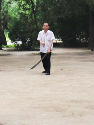 Man practicing with two Chinese swords.
