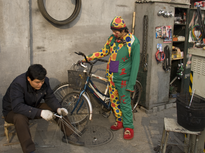 Beijing clown getting his bike fixed.