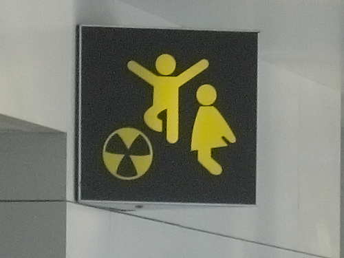 Sign with two sillouette children playing over a beachball that looks like the nuclear symbol.