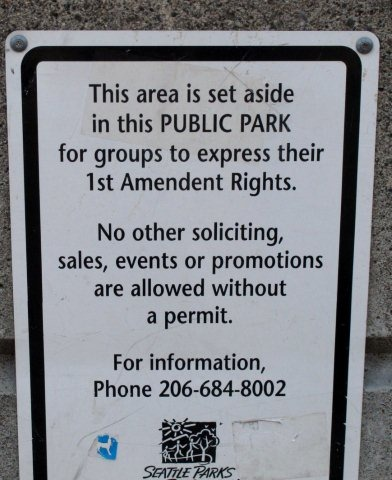 "A sign saying ""This area is set aside in this PUBLIC PARK for groups to express their 1st Amendment Rights."""