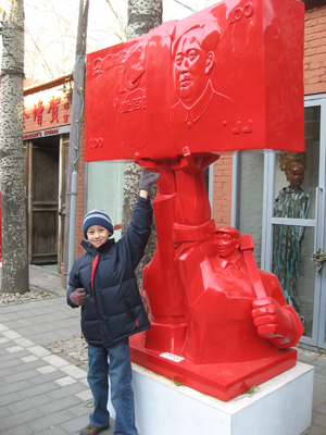 Andrew next to a statue of workers holding up 100 RMB notes.