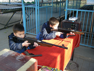 Andrew and Michael shooting rifles at an amusement park.