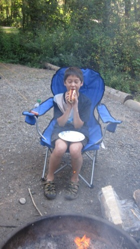 Andrew (13) enjoying a hotdog by the campfire.