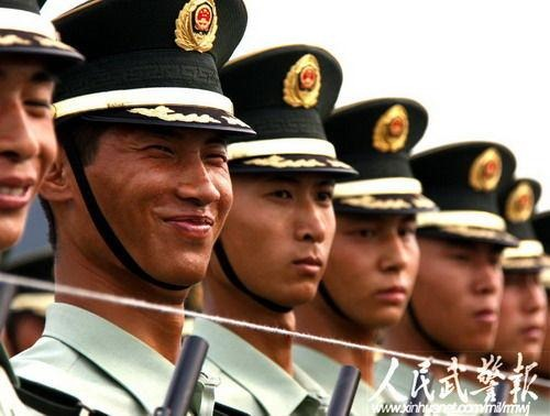 A row of soldiers faces with a string in front of them, just above their guns. One soldier is smiling.