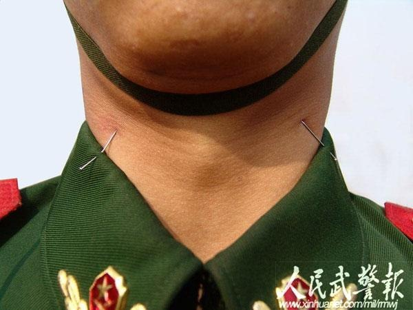 A closeup shot of the neck of one soldier, with sewing pins pushed up through his collar right up next to his neck, tips up.