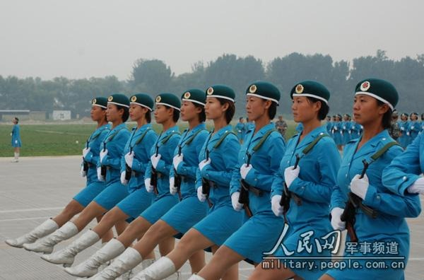 A line of female soldiers in blue jackets and skirts with white go-go boots.
