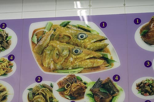 Photo of fish head curry, surrounded by other curries.