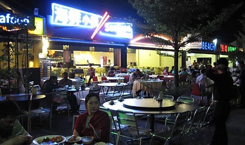 Outdoor tables lit by neon signs in Chinese