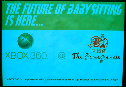 "Poster saying ""The Future of Babsitting is Here"" with the XBox 360 and ""The Pomegranate"" logos."