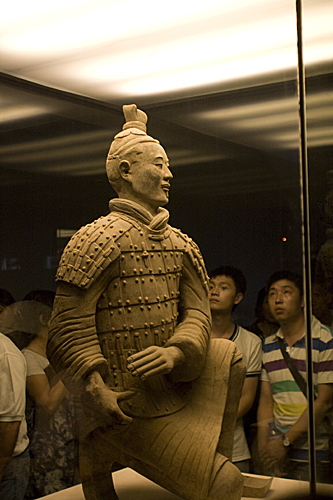 Two people looking at a terracotta solider close-up.