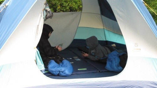 Andrew and Michael in sleeping bags playing cards in the tent. Both boys have hoodies on with the hoods up.