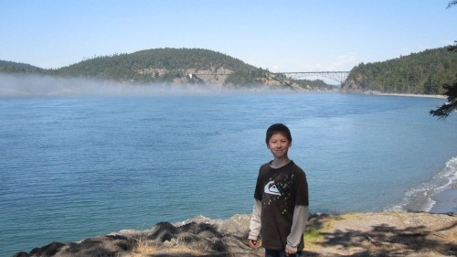 Andrew with Deception Pass Bridge behind him in the distance. There is a low fog over the water.