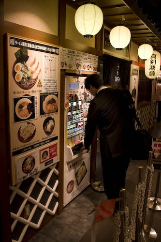 Ordering ramen from the machine at the ramen theme park.