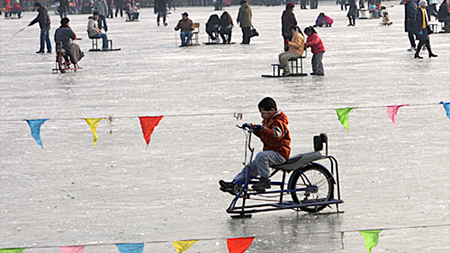 Kid riding an ice bike on Houhai.