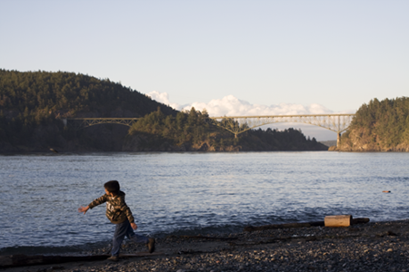 Michael throwing rocks into the water with the Deception Pass Bridge behind him at sunset.