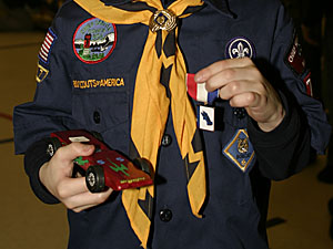 Andrew with his Pinewood Derby car and his third-place ribbon.