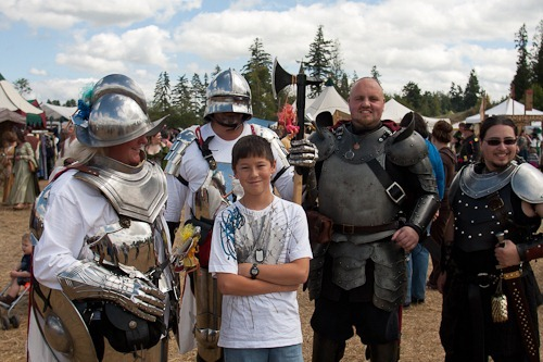 Andrew surrounded by four faire goers in armor.