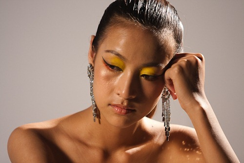 Headshot of a bored looking model with dramatic eye makeup with dangly ear rings.