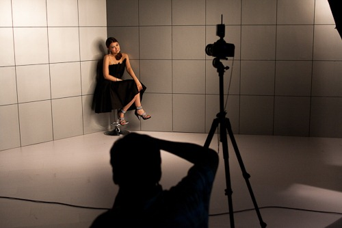 Silouette of a photographer shooting a seated model in a black dress.