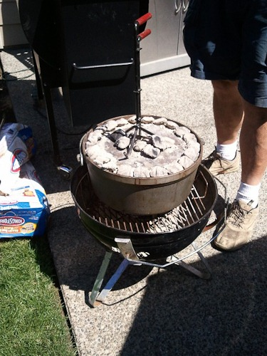 Dutch oven with charcoal on top, sitting on a low Weber grill.
